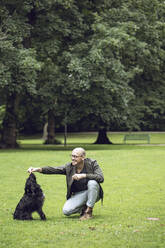 Man and his dog in a park - MCF00266