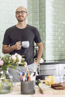 Man with a cup standing in the morning at home in the kitchen - MCF00281