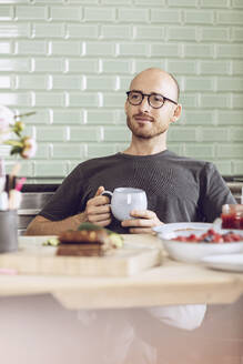 Man holding a cup sitting at the breakfast table at home - MCF00284
