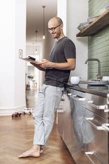 Man reading a magazine standing in the morning at home in the kitchen - MCF00287