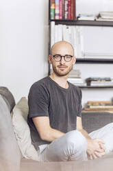 Man sitting at home on a couch - MCF00299