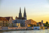 Saint Peter's Cathedral and Museum Brandhorst by Danube river against sky during sunset, Regensburg, Germany - LBF02675