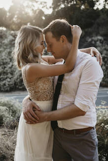Affectionate bride and groom hugging outdoors - LHPF00742