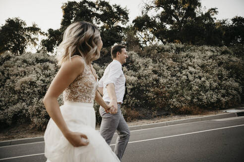 Bride and groom walking hand in hand on a country road - LHPF00754