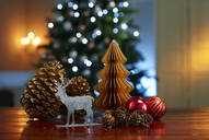 Close-up of various decorations on wooden table with illuminated Christmas tree in background at home - KSWF02088