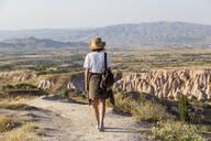 Woman walking to viewpoint near Uchisar, Cappadocia, Turkey - KNTF03310