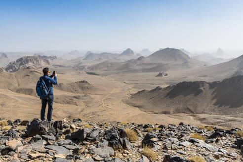 Man enjoying the mounains of Assekrem, Tamanrasset, Hoggar mountains, Algeria, North Africa, Africa - RHPLF07084
