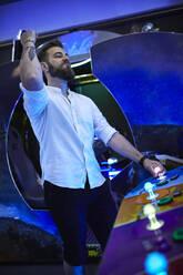 Man celebrating in an amusement arcade - ZEDF02569