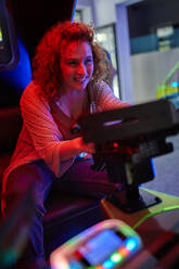Woman having fun with a driving simulator in an amusement arcade - ZEDF02572