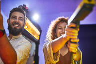 Happy couple playing and shooting with pistols in an amusement arcade - ZEDF02593