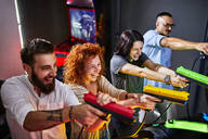 Happy friends playing and shooting with pistols in an amusement arcade - ZEDF02599