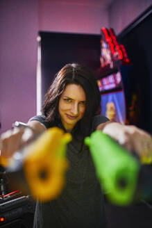 Portrait of smiling woman shooting with pistols in an amusement arcade - ZEDF02602