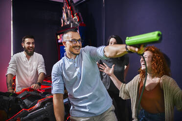 Happy friends playing and shooting with pistols in an amusement arcade - ZEDF02605