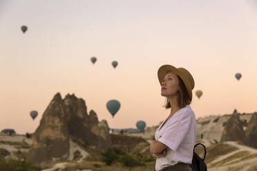 Young woman and hot air ballons, Goreme, Cappadocia, Turkey - KNTF03313