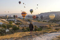 Young woman and hot air ballons, Goreme, Cappadocia, Turkey - KNTF03319