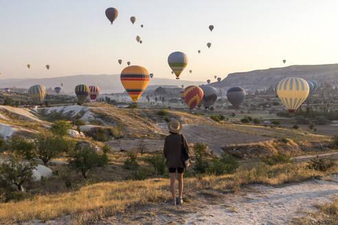 Young woman and hot air ballons, Goreme, Cappadocia, Turkey - KNTF03319