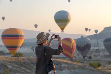 Young woman and hot air ballons, Goreme, Cappadocia, Turkey - KNTF03322