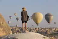 Young woman and hot air ballons, Goreme, Cappadocia, Turkey - KNTF03325