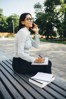 Young businesswoman sitting on a bench talking on cell phone and taking notes - OYF00035