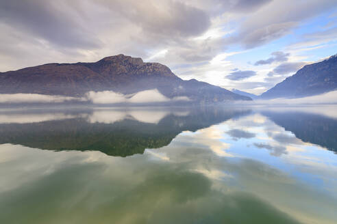 Mountains reflected in Lake Mezzola at dawn shrouded by mist, Verceia, Chiavenna Valley, Lombardy, Italy, Europe - RHPLF07472