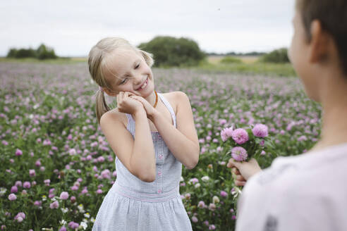 Boy giving a clover flowers to smiling girl - EYAF00402