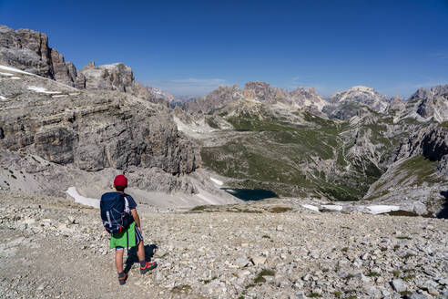 Rear view of boy with backpack looking at Tre Cime Di Lavaredo against blue sky, Veneto, Italy - LOMF00901