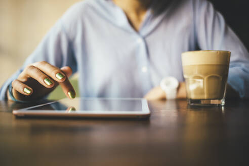 Woman sitting in a cafe using a digital tablet and drinking a coffee - OYF00054