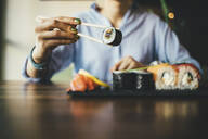 Close-up of a woman eating sushi in a restaurant - OYF00057