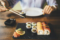 Close-up of a woman eating sushi in a restaurant - OYF00060