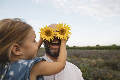 Daughter covering eyes of father with sunflowers - KMKF01056