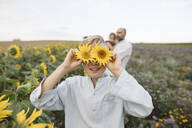 Playful boy covering his eyes with sunflowers in a field with family in background - KMKF01062