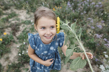 Portrait of happy girl with a sunflower in a field - KMKF01071