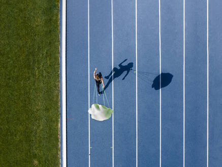 Top view of female runner with parachute on tartan track - STSF02206