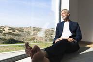 Senior businessman sitting at panorama window with closed eyes - SBOF02000