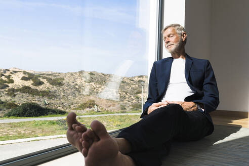 Senior businessman sitting at panorama window with closed eyes - SBOF02000