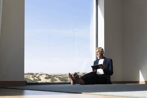 Senior businessman sitting at panorama window using tablet - SBOF02003