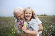 Portrait of laughing grandfather and granddaughter with picked flowers on a meadow - EYAF00426