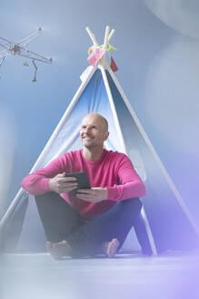 Smiling man flying drone in children's room - KSHSF00005
