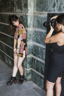 Young woman wearing patterned dress posing for a photo shoot - LJF00932