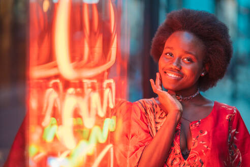 Smiling young woman standing next to neon light - DLTSF00001