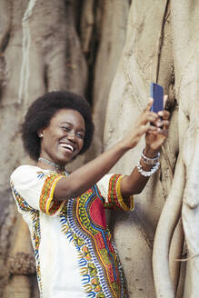 Laughing young woman taking a selfie with a smartphone - DLTSF00018