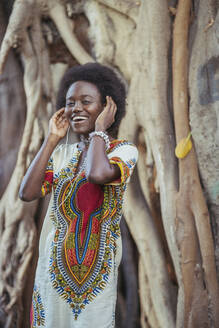 Smiling young woman standing in front of a tree trunk wearing earphones - DLTSF00030