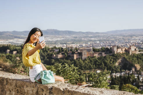 Smiling young woman taking a selfie at the Alhambra, Granada, Spain - LJF00961