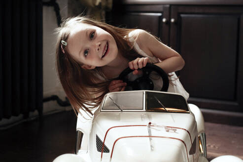 Cute little girl driving her toy car - EYAF00438