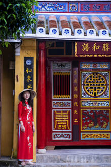 A young Vietnamese woman wearing a traditional Ao Dai dress and standing outside a temple in the historic town centre, Hoi An, Vietnam, Indochina, Southeast Asia, Asia - RHPLF08532