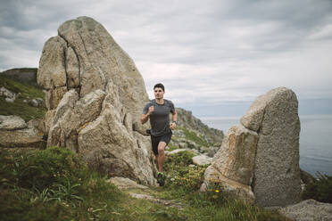 Trail runner in coastal landscape, Ferrol, Spain - RAEF02278