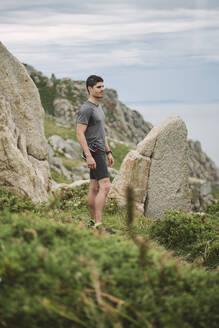 Trail runner standing in coastal landscape, Ferrol, Spain - RAEF02281