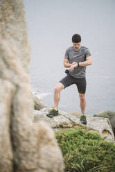 Trail runner standing in coastal landscape looking at his watch, Ferrol, Spain - RAEF02284