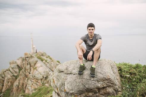 Portrait of trail runner sitting on a rock in coastal landscape, Ferrol, Spain - RAEF02287