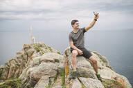 Trail runner sitting on a rock in coastal landscape taking a selfie, Ferrol, Spain - RAEF02290